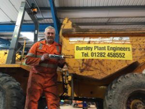 Photo of Burnley Plant Engineers Fitter with tube of TTP Probond sealer and bonder beside a dumper machine