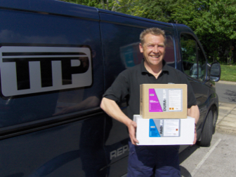 TTP salesman carrying boxes of TTP Duraslip and TTP Radfix non clog radiator stop leak with TTP van in background