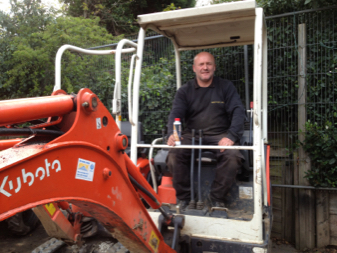 photo of driver in a mini digger holding a bottle of TTP Fuel treatment part number FT900