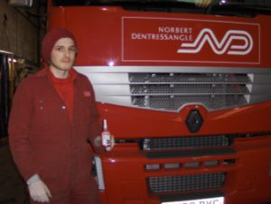 fitter in front of Norbert Dentressangle red truck holding a bottle of TTP thread lock part number TLK2003