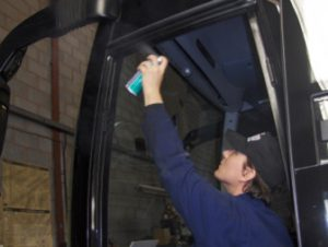 HGV fitter applying TTP dry silicone lubricant to coach plug door part number DS100
