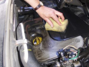 dirty engine cover being cleaned with TTP PROCLEAN solvent degreaser