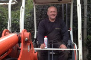 photo of driver in mini digger holding bottle of TTP Oilfix Oil Stop Leak part number OLF0015