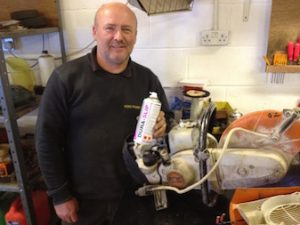 Photo of fitter with can of TTP DURA-SLIP PTFE lubricant spray and angle grinder